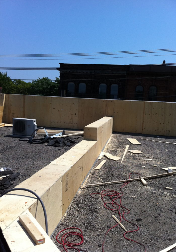 Framing old brick wall parapet with plywood